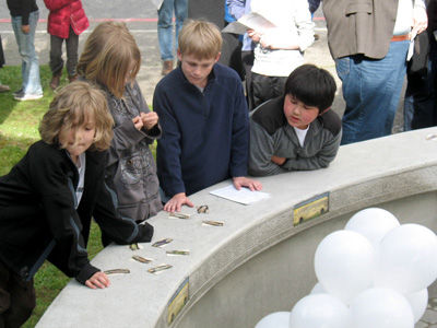 Matias Solberg, Liam Solberg, Gavin Jakubik and Mitchell Melby lean on a new bench at Ordway Elementary honoring slain school counselor Jeffrey McKinstry.