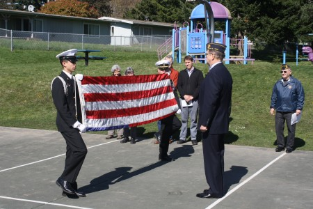 Ethan Fowler/Special to the Kitsap Sun Members of Bremerton High School's Navy JROTC unit present American Legion Post 172 Commander Fred Scheffler with an American flag that once was previously used on the USS Alabama submarine at Bangor to conclude the Government Way decommissioning ceremony.