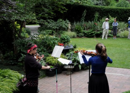 Contributed photo / Dave Gibson From left, violinists Lia Hardy and Lea Fetterman perform during last year's Bainbridge in Bloom garden tour.