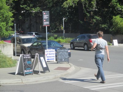 Photo by Ethan Fowler / Special to the Kitsap Sun A pedestrian crosses Ericksen Avenue as he walks along Winslow Way next to a number of business sandwich boards.