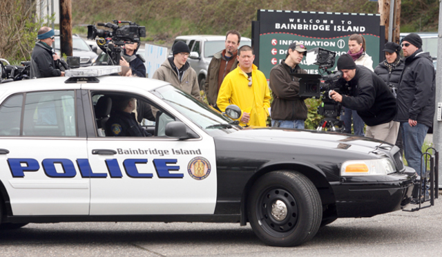 An America's Most Wanted television crew sets up in the intersection of Winslow Way and Highway 305 on Bainbridge Island Thursday morning. In the police car is Bainbridge Island Police Officer Steve Cain who was involved in the car chase.