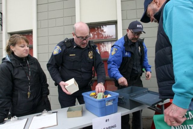 Bainbridge Island Police Department evidence technician Jennifer Cooper, Lt. Chris Jensen and Reserve Officer Mark Crowthers inspect ammunition turned in by a Bainbridge resident in 2013. TAD SOOTER / KITSAP SUN