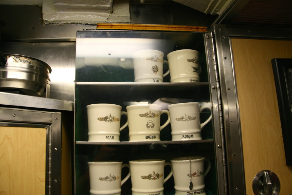 Coffee mugs, and on top of them, Richard O'Kane's famous cribbage board.