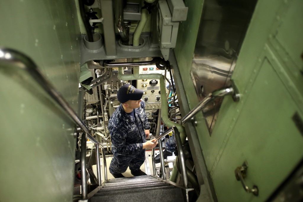 USS Seawolf sailor Garrett Guglielmetti at the bottom of a narrow passage with steep stars on the boat. LARRY STEAGALL / KITSAP SUN