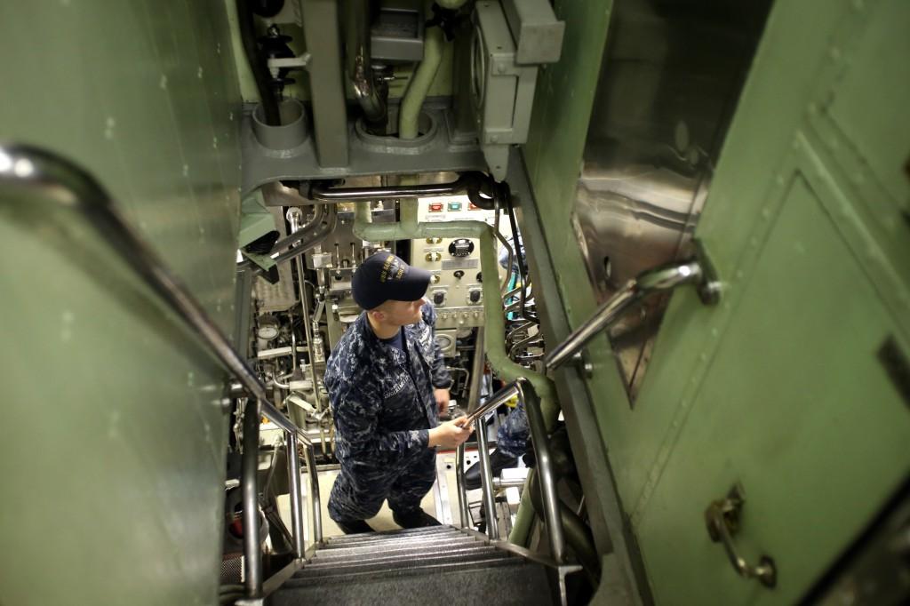 USS Seawolf sailor Garrett Guglielmetti at the bottom of a narrow passage with steep stars on the boat. LARRY STEAGALL / KITSAP SUN