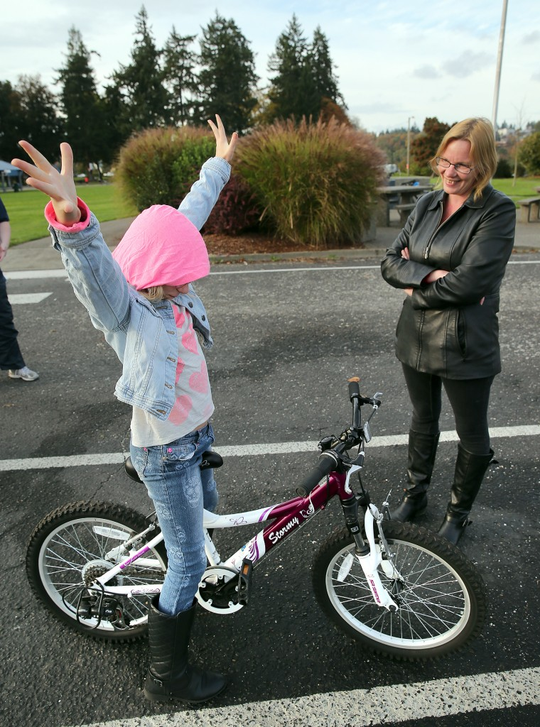 Alexandra Funari, 10, celebrates after she rode her new bike at Evergreen-Rotary Park in Bremerton on Wednesday. To her right is her mom, Bonnie Flacco. LARRY STEAGALL / KITSAP SUN