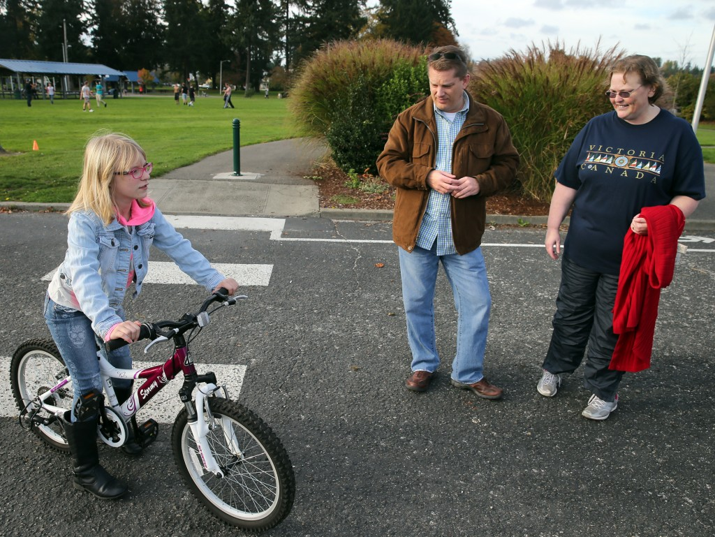 Alexandra with her new bike. In the center is Tom Kalmbach of Renton, who gave her the bike, and Joanne Jogerst who contacted Tom. LARRY STEAGALL / KITSAP SUN