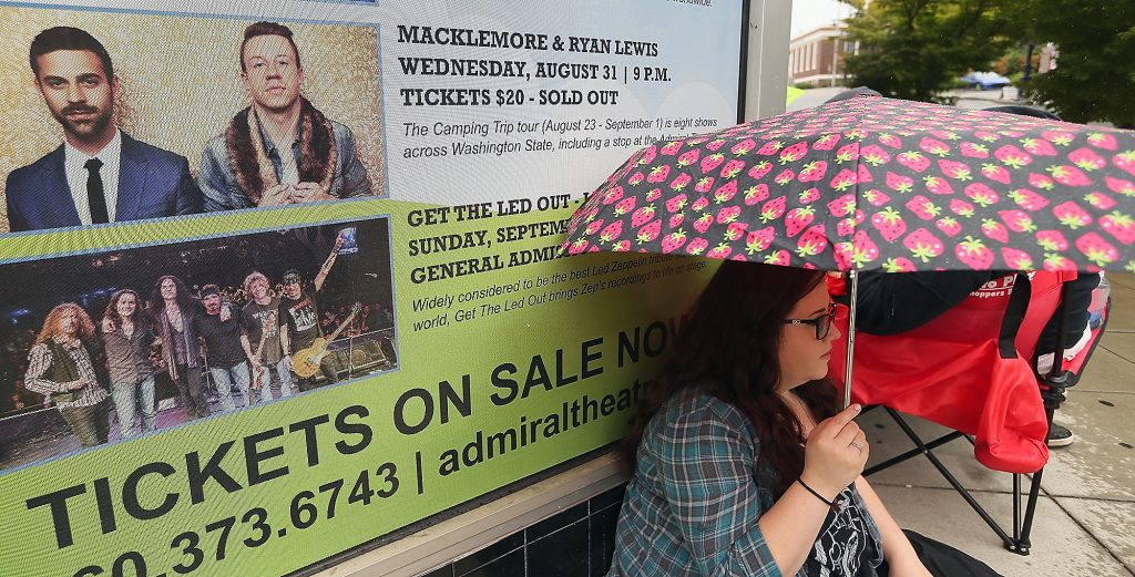 Jennifer Heath, 23, of Federal Way, sits in front of the sign adorned with Macklemore and Ryan Lewis as she and fellow fans brave the rain and wait in line in front of the Admiral Theatre in Bremerton on Wednesday, August 31, 2016. (MEEGAN M. REID / KITSAP SUN)