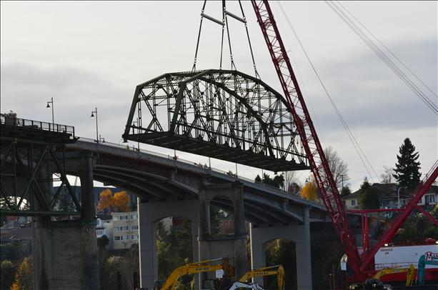 The old bridge's truss comes down. The company that did the work recycled the old span. Yet some of its steel is still a fence in Manette.