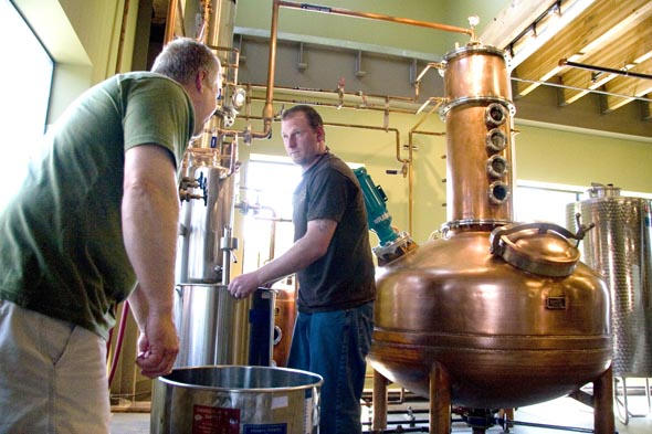 Keith Barnes, left, helps his son Patrick change out the container that catches the distilled product at the business they've started, Bainbridge Organic Distillery.