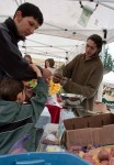 Caleb Heinig of Colinwood Farm of Port Townsend sells greens to a customer during openign day at Poulsbo Farmers Market.