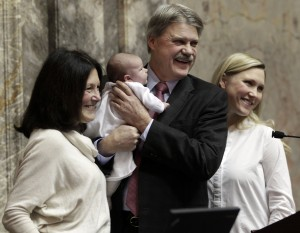 Standing at the rostrum Washington state Senator and soon-to-be-defeated in his bid to repeat as Senate President Pro Tem Tim Sheldon gets a photo taken by staff photographer Aaron Barna holding his new grand-daughter Scarlett born on Dec.13. 2014, while joined by his wife Linda and daughter Alex on Monday, Jan. 12, 2015, during the opening day for the 2015 legislative session in Olympia. (AP Photo/The Olympian, Steve Bloom)