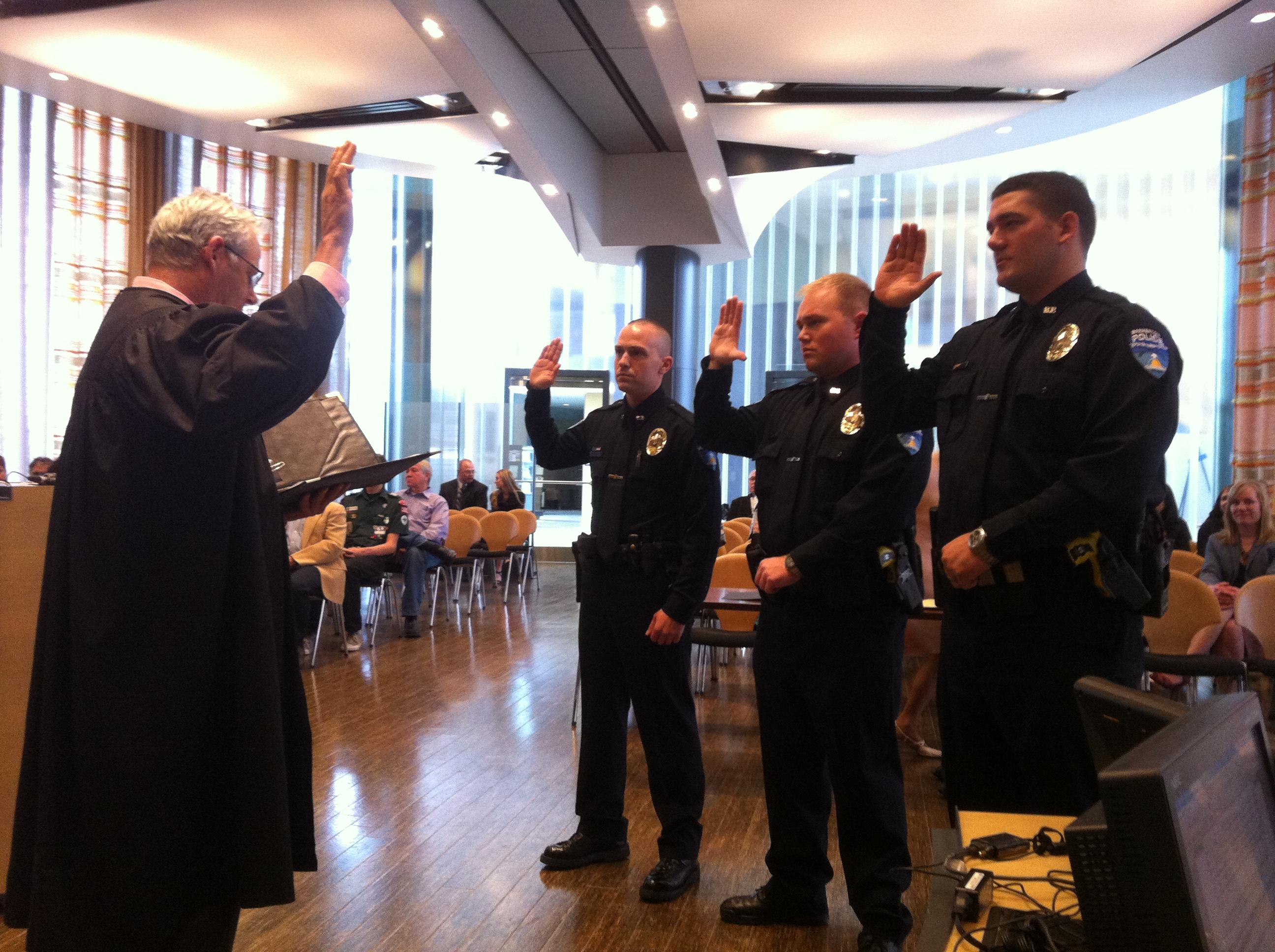 Bremerton Municipal Court Judge James Docter swears in the city's three new police officers Wednesday. Photo by Shannon Corin.