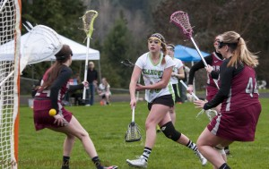 Klahowya junior Cassidy Andrews shoots through a pair of Bethel defenders Thursday in a Washington Schoolgirls Lacrosse game at CK Junior High in Silverdale. Photo: Kurt DeVoe