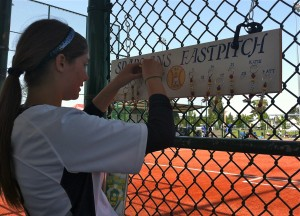 """Bainbridge center fielder Kate Kinney places her """"mental check-in"""" keychain on the Spartans' board before their elimination game against Liberty of Issaquah at the Class 3A state softball tournament at the RAC in Lacey. The board is a signal to the coaches and players that each one is ready for their game and mentally checked in. (Annette Griffus   Kitsap Sun)"""