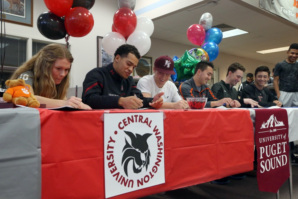 Central Kitsap student athletes (left to right) Michaela Wallitner, Kendal Yaegle, Nolan Wiler, Jaeger Skifstad, Griffith McCormick and Aki Buckson sign their letters of intent on Wednesday, February 3, 2016. (MEEGAN M. REID / KITSAP SUN)