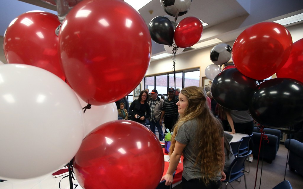Central Kitsap student athlete Michaela Wallitner is framed by balloons as she leaves the table after signing her letter of intent to play soccer at Central Washington, on Wednesday, February 3, 2016. (MEEGAN M. REID / KITSAP SUN)