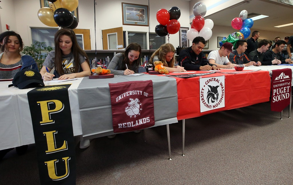Central Kitsap student athletes (left to right) Hope Lawrence, Elise Freund, Melissa Johnson, Michaela Wallitner, Kendal Yaegle, Nolan Wiler, Jaeger Skifstad, Griffith McCormick and Aki Buckson sign their letters of intent on Wednesday, February 3, 2016. (MEEGAN M. REID / KITSAP SUN)
