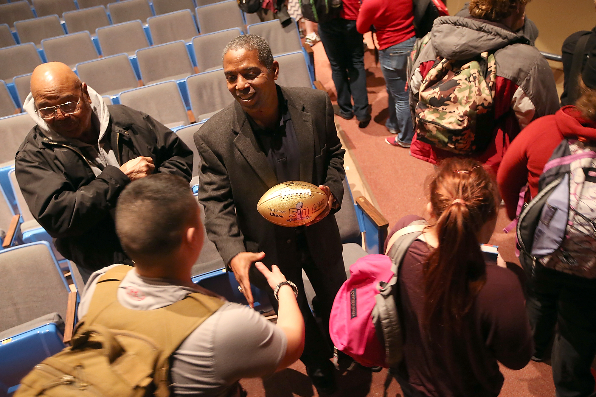 Bremerton High Alumni Tony Boddie shakes hands with students while holding a gold football commemorating his trip to the Super Bowl with the Denver Broncos that was presented to him during an assembley at the school on Friday, February 5, 2016. (MEEGAN M. REID / KITSAP SUN)