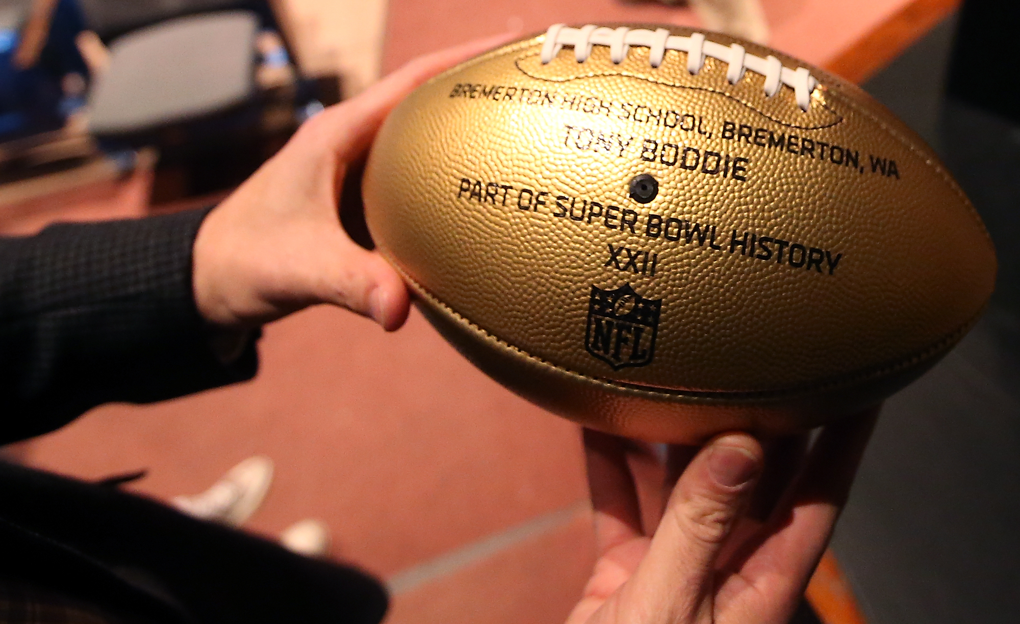 Bremerton High School principal John Polm holds alumni Tony Boddie's gold football commemorating his trip to the Super Bowl with the Denver Broncos. (MEEGAN M. REID / KITSAP SUN)