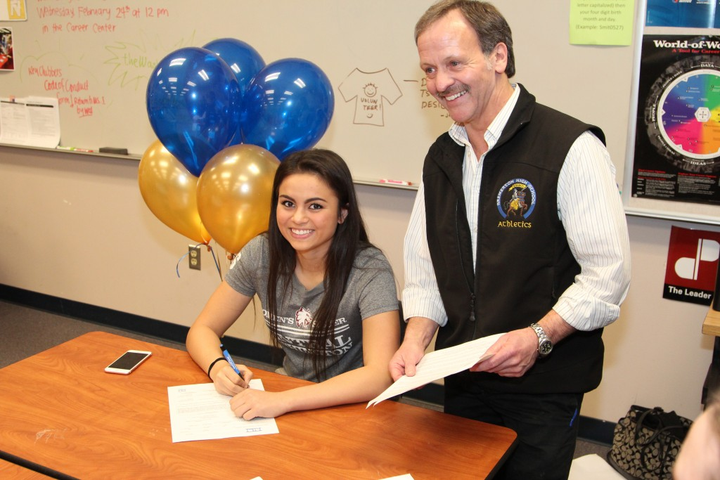 Bremerton soccer player Alyssa Beach signed her national letter of intent Wednesday with Central Washington. At right is Bremerton athletic director Jeff Barton.