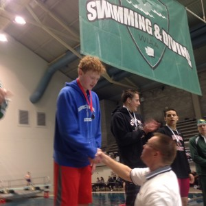 Olympic freshman Ross Burchell receives his second-place medal from Les Schwab representative Lonnie Nunley Saturday for the 200-yard freestyle. (Annette Griffus | Kitsap Sun)