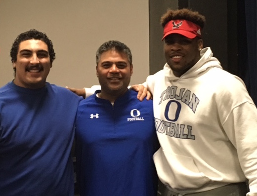 Olympic's Alberto Castorena (left) and Keith Moore (right) pose with Trojans football coach Sal Quitevis for during a signing day ceremony at the school.