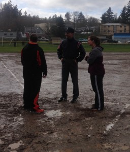 Umpire Brian Streege talks with CK assistant coach Holly Carver and SK head coach Mindi Outhwaite as their softball game was suspended in the bottom of the second inning Tuesday at Linder Field. (Annette Griffus | Kitsap Sun)