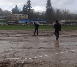 The umpiring crew check out Linder Field after play between South Kitsap and Central Kitsap was suspended in the bottom of the second inning during a non-league softball game Tuesday in Silverdale. (Annette Griffus | Kitsap Sun)