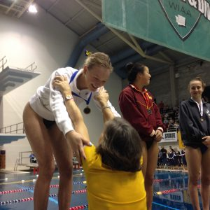 Bainbridge senior Zora Opalka receives her gold medal from Spartans head coach Sarah Bullock at the Class 3A state swimming and diving meet. Opalka is the first female diver to win a state championship for Bainbridge. (Annette Griffus/Kitsap Sun)
