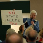 "League President Catherine Ahl displays ""No State Income Tax"" sign brought by some attendees at the League's forum at the Eagle's Nest in Bremerton on Wednesday."