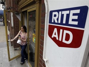 FILE- In this June 20, 2011, file photo, a woman exits a Rite Aid store, in Philadelphia. The Wall Street Journal said Walgreens Boots Alliance is in advanced talks to buy Rite Aid. Walgreens declined to comment Tuesday, Oct. 27, 2015, when contacted by The Associated Press. The deal would combine the largest and third-largest U.S. drugstore chains, based on store counts. (AP Photo/Matt Rourke, File)