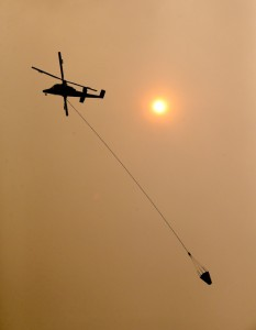 "A firefighting helicopter flies past a dark red sun and through a deep haze that blanketed the Okanogan Valley Saturday, Aug. 22, 2015, in Tonasket, Wash. Out-of-control blazes in north-central Washington have destroyed buildings, but the situation is so chaotic that authorities have ""no idea"" how many homes may have been lost. (AP Photo/Elaine Thompson)"