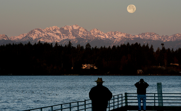 Camera buffs come out early to get a photo as the full moon begins to set on Wednesday as the sunrise hits the Olympic Mountains on a clear and cold day from the Lions Park Dock in Bremerton. (LARRY STEAGALL | KITSAP SUN)