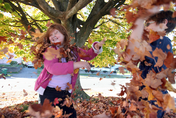 Erynn Jensen,9,left, tries to dodge the dry leaves that her neighbor Robert Schauger,13, tosses at her. They are playing under a big tree losing it's leaves at 11th and Ohio in Bremerton. Jensen, and Schauger take pride in raking the leaves up and making neat piles after playing in them. (LARRY STEAGALL | KITSAP SUN)