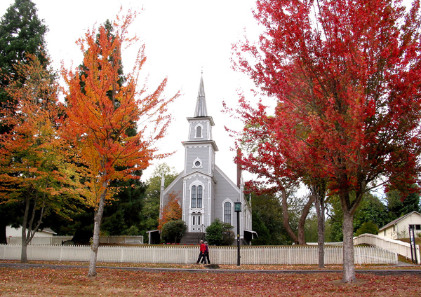 In a scene that looks like and East Coast Fall. The trees in front of Saint Paul's Episcopal Church in Port Gamble are a palate of fall colors, as a couple walks by on Tuesday. The church was built in 1870. The Church is modeled after The Congregational Church in East Machias, Maine. (LARRY STEAGALL / KITSAP SUN)