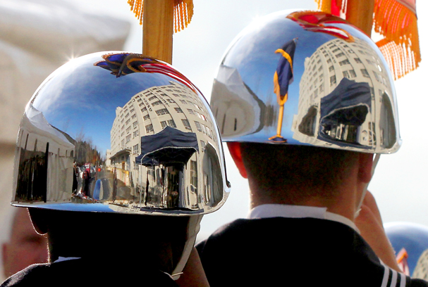 The Kela Logistics Center is reflected in the helmets of Naval color guard members Michael Kibosio and Clinton Scott as they present the colors during the dedication ceremony at Naval Base Kitsap. MEEGAN M. REID | KITSAP SUN