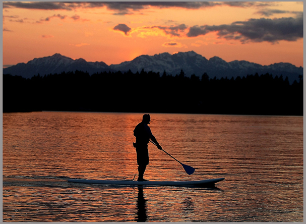 Dave Petersen glides through the water on his paddle board as the sun sets over Dyes Inlet on Wednesday. (MEEGAN M. REID/KITSAP SUN)