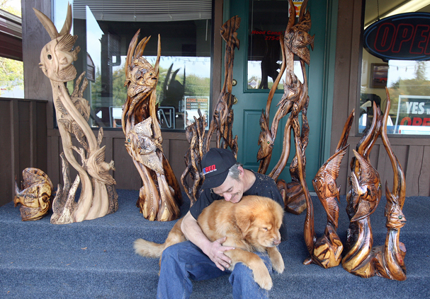 Jerry Tallman of Belfair and his dog Salty with some of his seascapes he has carved with a chainsaw on Monday. Tallman lost his arm in a logging accident, but still carves. He is going to display them at the Seattle Aquarium. LARRY STEAGALL / KITSAP SUN