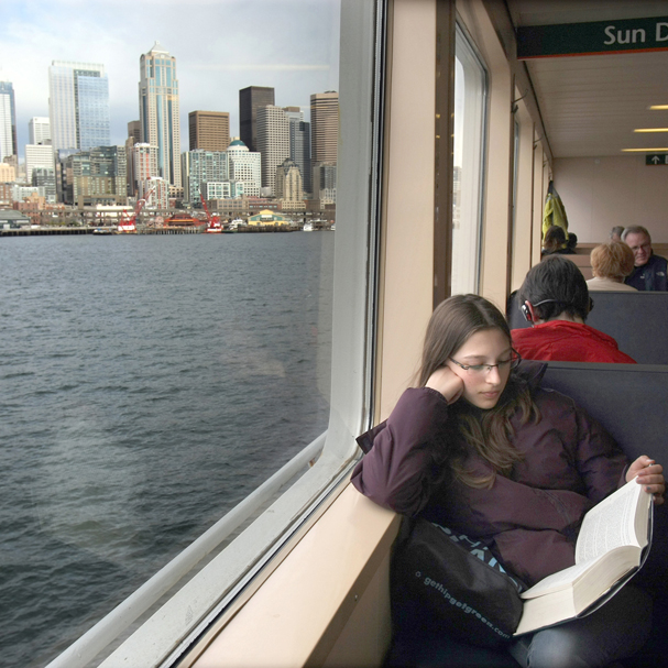 Josephine Forney,12, of Bainbridge Island reads her book as the ferry approaches Seattle. (LARRY STEAGALL / KITSAP SUN)