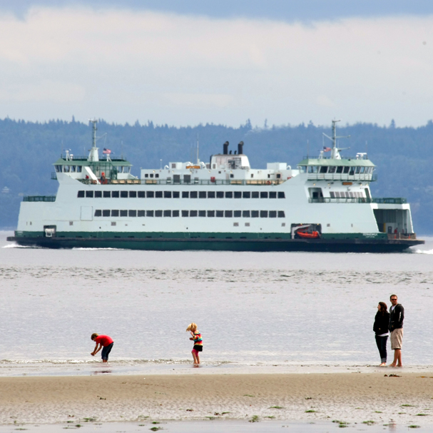 Beach goers stroll along the shore as the a ferry sails past in Port Townsend. (LARRY STEAGALL / KITSAP SUN)