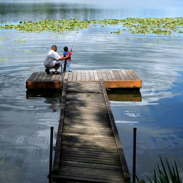 Angelo Cruz and his son Tre, 3, off of one of the docks at Kitsap Lake Park in Bremerton. (MEEGAN M. REID / KITSAP SUN)