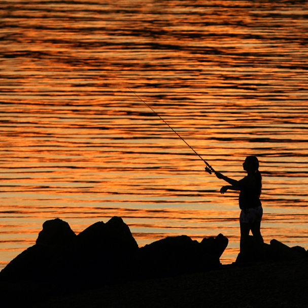 A fisherman casts her line at sunset at the Pat Carey Vista in East Bremerton. (LARRY STEAGALL / KITSAP SUN)