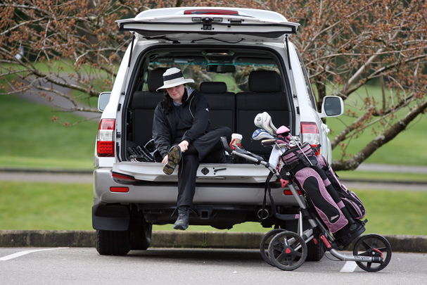 Tracy Huntley of Seabeck uses the back of her SUV to get ready for her golf lesson Monday at the Gold Mountain Golf Club. (LARRY STEAGALL / KITSAP SUN)