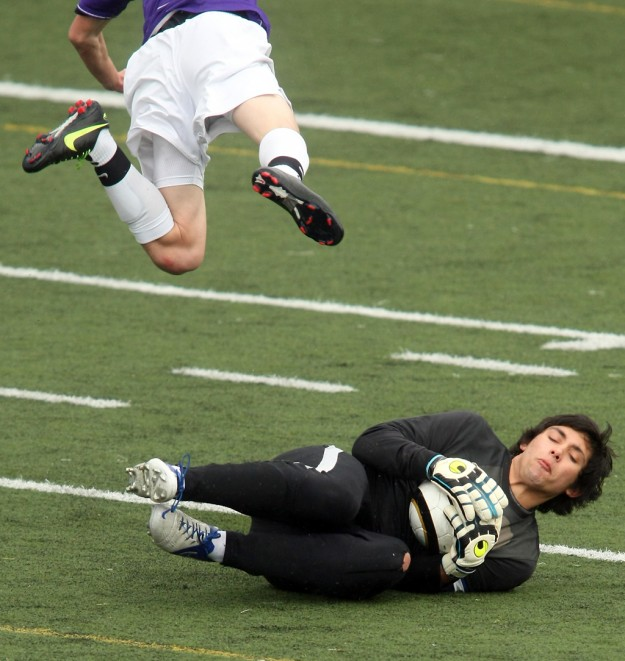 Olympic goalie Harry Hanson stops a shot by North Kitsap's Brady Sparrow at Silverdale Stadium on Friday, April 12, 2013. (MEEGAN M. REID / KITSAP SUN)