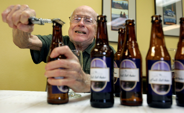Bay Pointe Retirement Community resident Al Cook, 92, uses all his strength to pop the cap off a bottle of beer. Cook is one of the brew club commissioners at the facility and the club held a tasting party for the first batch of beer that they made on Tuesday. (LARRY STEAGALL / KITSAP SUN)