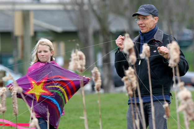 Bruce Beckwith, untangles a kite from the cattails for his granddaughter Wendy Beckwith, 9, at Silverdale Waterfront Park on Tuesday. (LARRY STEAGALL / KITSAP SUN)
