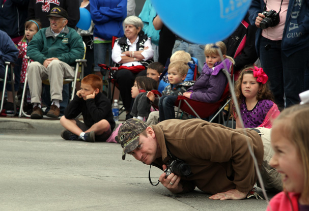 Aaron Ross, of Bremerton, lays down on the street to get a view of what entry is coming up next in the Armed Forces Day Parade. (STEVE ZUGSCHWERDT / SPECIAL TO THE KITSAP SUN)