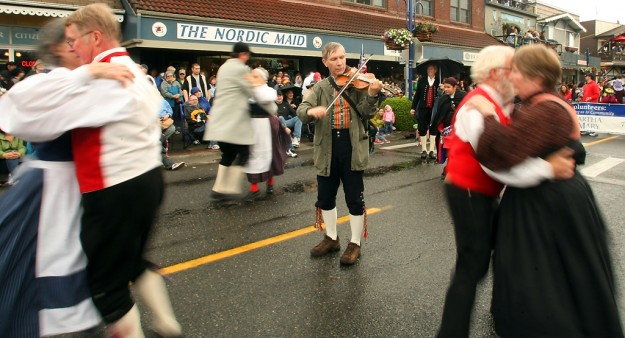 A fiddler plays as the Leikarringen dancers twirl down the street during the Viking Fest Parade through downtown Poulsbo on Saturday, May 18, 2013. (MEEGAN M. REID / KITSAP SUN)