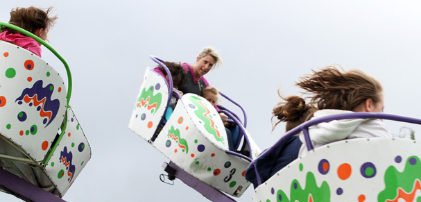 Jeanene Nover, of Poulsbo, hangs on to her children Sophie and Tessa as they braved the octopus ride at the Viking Festival Carnival. (STEVE ZUGSCHWERDT / SPECIAL TO THE KITSAP SUN)